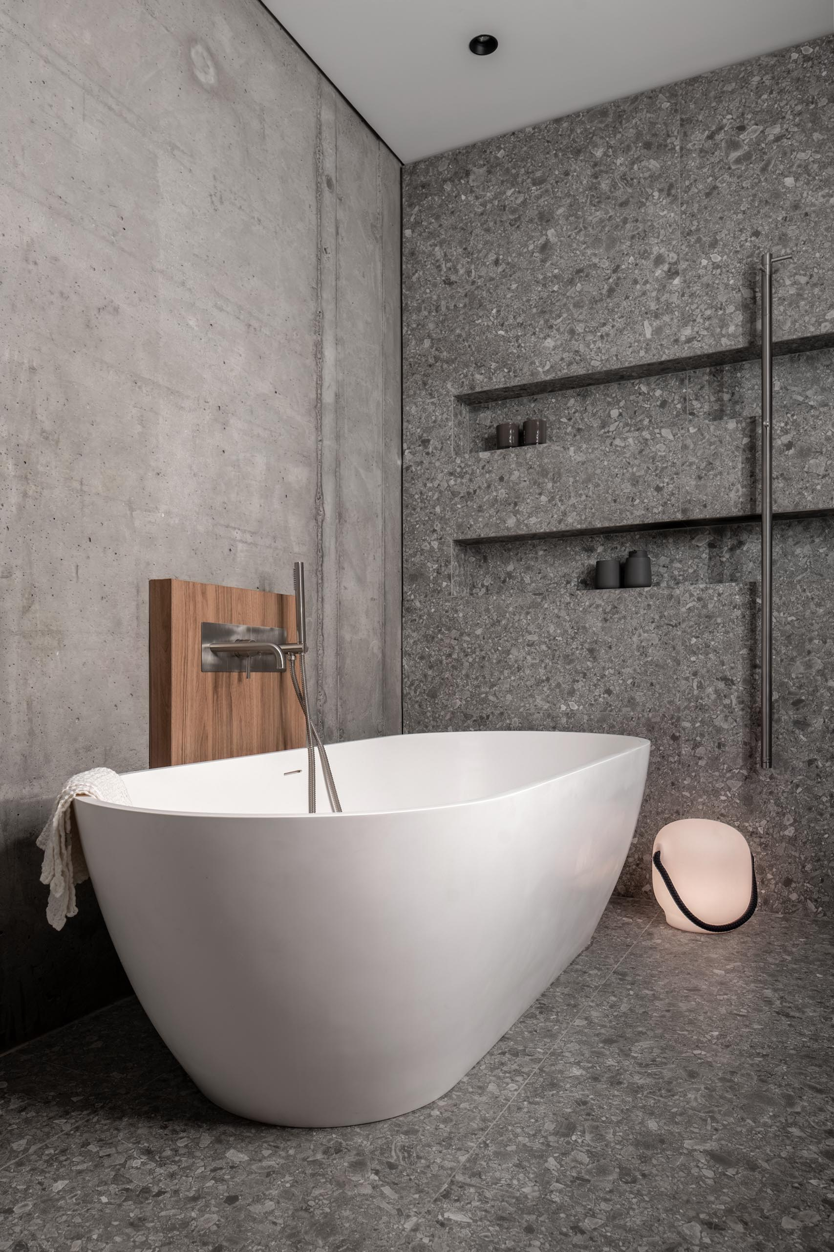 A modern grey bathroom with two shower niches, and a freestanding white bathtub.