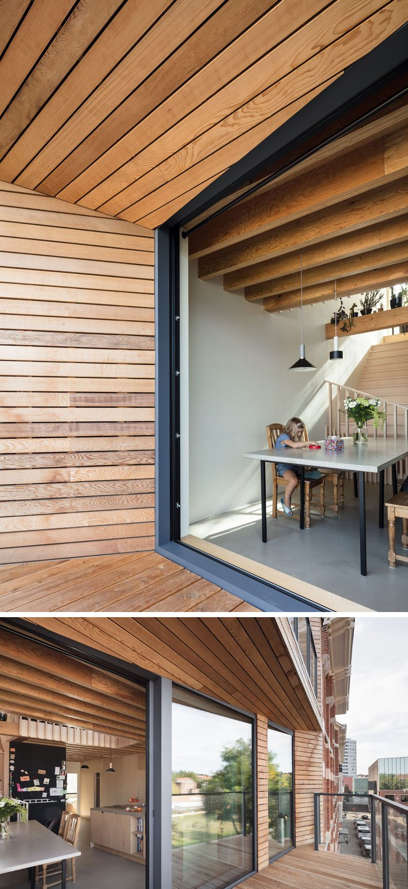 The dining area and kitchen of this modern house open up to the partially covered balcony that overlooks the city. #Balcony #ModernBalcony #WoodLinedBalcony
