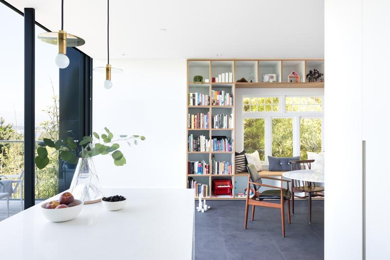 This modern house has a wood framed built-in window seat that's surrounded by open shelving, creating places to store books, decorative items, and toys. #WindowSeat #Shelving #InteriorDesign #DiningRoom