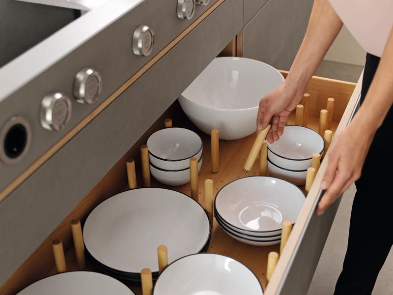 Instead of keeping plates and bowls in cupboards this kitchen drawer design has wood separators that can be moved depending on the size of the dinnerware. #KitchenOrganization #KitchenDrawers #DinnerwareStorage