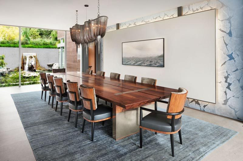 This modern dining room showcases statement pieces like a large dining table, a sculptural light, a backlit wall, and artwork. #DiningRoom #Art #ModernInterior