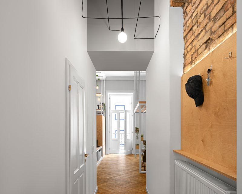 The hallway in this apartment has glimpses of the original brick construction, leads from the entryway to the main living area and bedrooms. #Hallway #InteriorDesign