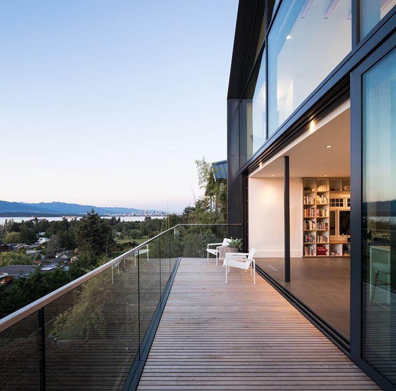 This modern living area has large sliding glass doors that open up to a balcony with a glass railing. #Balcony #Architecture