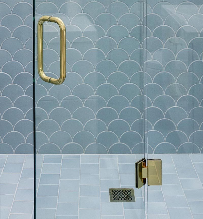 In this modern bathroom, In the shower, scalloped tiles (also known as fish scale tiles) that transition from white on the upper half of the shower, into blue tiles that line the lower half. Both the scalloped tiles wrap around the walls of the bathroom. #BathroomTiles #ModernBathroom #ScallopedTiles