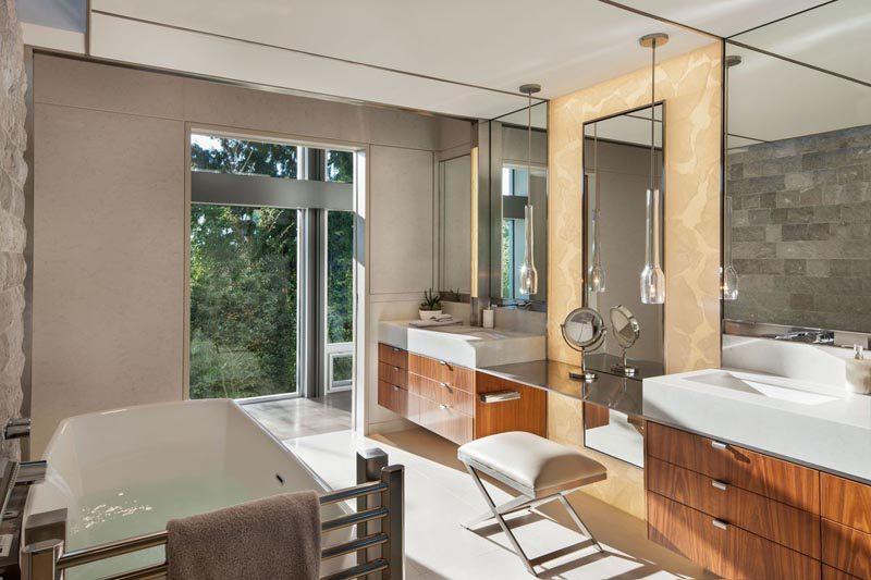 In this modern master bathroom, a makeup vanity lies between two bathroom vanities, while a freestanding bathtub is located on the opposite wall. #MasterBathroom #BathroomDesign