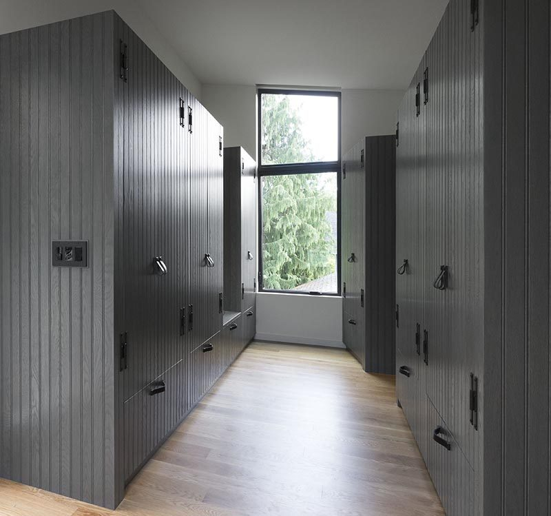 This modern walk-through closet has custom wood cabinetry with a dark gray wood paneling finish. A tall window at the end of the closet keeps the space bright, while a gap in the closet on the left hand side acts as a small bench or place to put your outfit when getting ready. #WalkThroughCloset #WalkThroughWardrobe #MasterSuite #Closets #Cabinets #DarkGreyCabinets