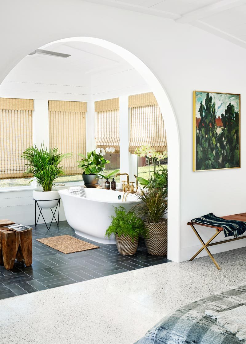 This sunroom, located off the bedroom, has been outfitted with a freestanding tub that enjoys expansive views to the wide open lawn of the backyard. #Sunroom #Bedroom #BathroomDesign