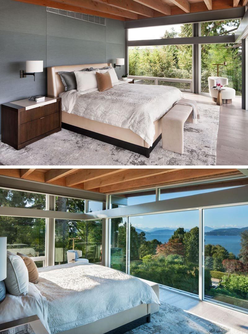 This modern master bedroom has a grey accent wall and windows that look out to the water and mountains in the distance. #MasterBedroom #Windows