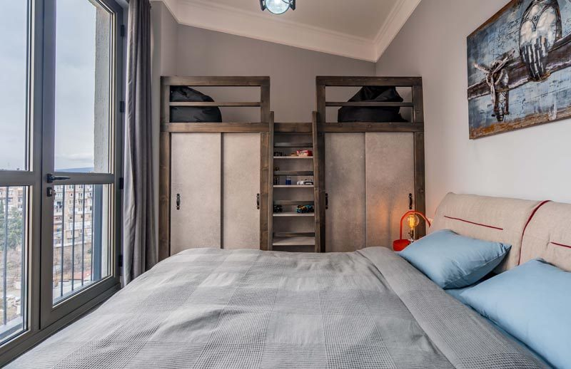 This modern bedroom has a lofted sitting area above the closets, that's accessed by a small ladder and furnished with beanbags. #LoftedLounge #BedroomDesign #BedroomIdeas #ModernBedroom #Loft #Closets