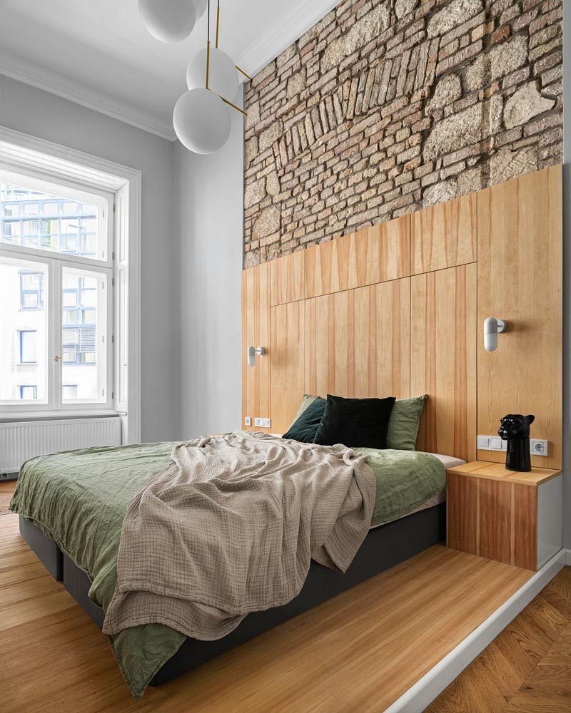 This modern apartment has a bedroom with high ceilings that allow the original brick and stone work to be shown, while the bed has been placed on a platform, designating the sleeping area. #Bedroom #ModernBedroom #BedroomDesign