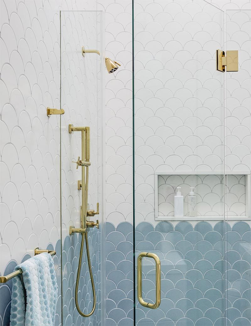 This modern bathroom has gold hardware found through the bathroom, like the towel holder, the supports that hold the glass shower screen in place, the shower head, taps, and hand-held shower. #ModernBathroom #BathroomDesign #GoldBathroomHardware