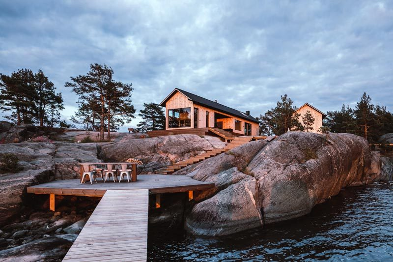 Steps lead from this modern holiday house down to a deck that's nestled between the rocks, and attaches to a small jetty. #Landscaping #Deck #ModernCabin