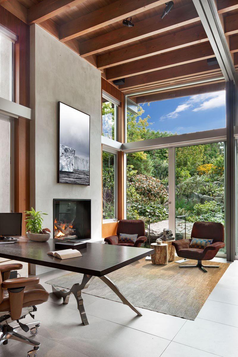 This modern den has high ceilings, a built-in fireplace, and a sliding door that opens to the garden. #ModernDen #ModernHomeOffice