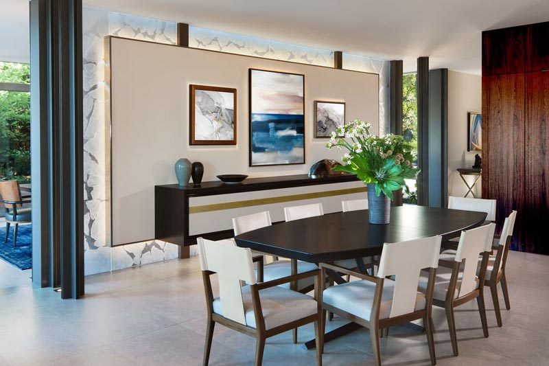 This modern dining room has a wall specifically designed to display artwork. #DiningRoom