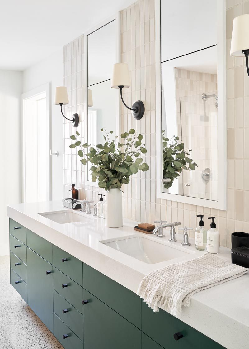 In this modern bathroom, there's a matte deep green vanity with dual sinks, while two vertical white-framed mirrors hang on a light colored tiled wall that also matches the tiles the shower. #ModernBathroom #GreenVanity #VanityIdeas #VerticalMirrors #TielsWalls