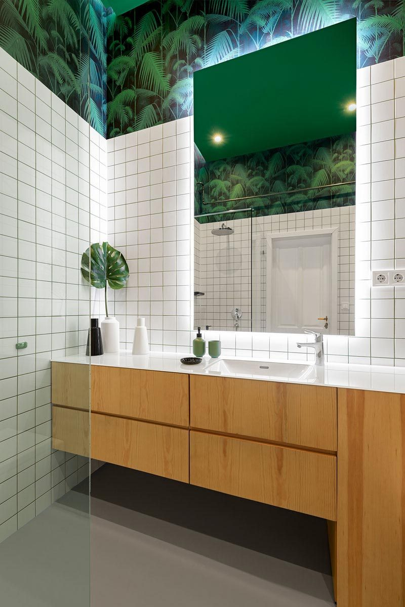 This modern bathroom has been decorated with square white tiles, a wood vanity, decorative wall coverings in a palm tree pattern, and a mirror with back-lighting. #Bathroom #ModernBathroom #GreenWhiteBathroom
