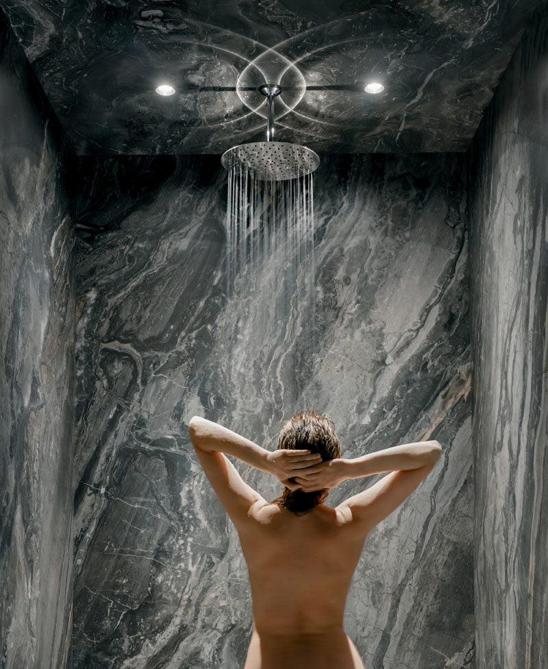 In this modern bathroom, dark marble covers the shower walls and ceiling, while a rainfall shower head is highlights by two mini spotlights. #DarkBathroom #DarkShower #ModernBathroom #RainfallShower