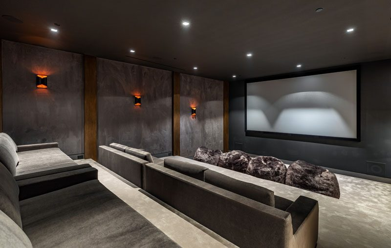 This modern house has a home theater that's been furnished with grey stadium seating and bean bags. #HomeTheater #StadiumSeating