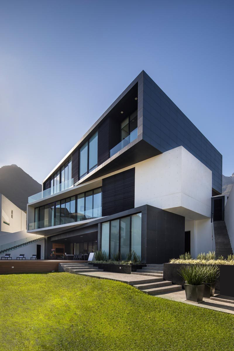 The three rectangular volumes have been rotated and shifted to create a more angled appearance for this modern house, with the lighter middle section separating the two darker levels. #ModernArchitecture #ModernHouse #HouseDesign #Balconies