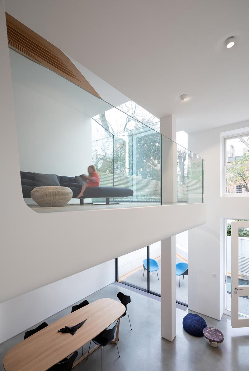 This modern house has a sitting room that opens up to a space with a couch with views of the garden and the lower level of the home. #GlassRailing #SittingRoom