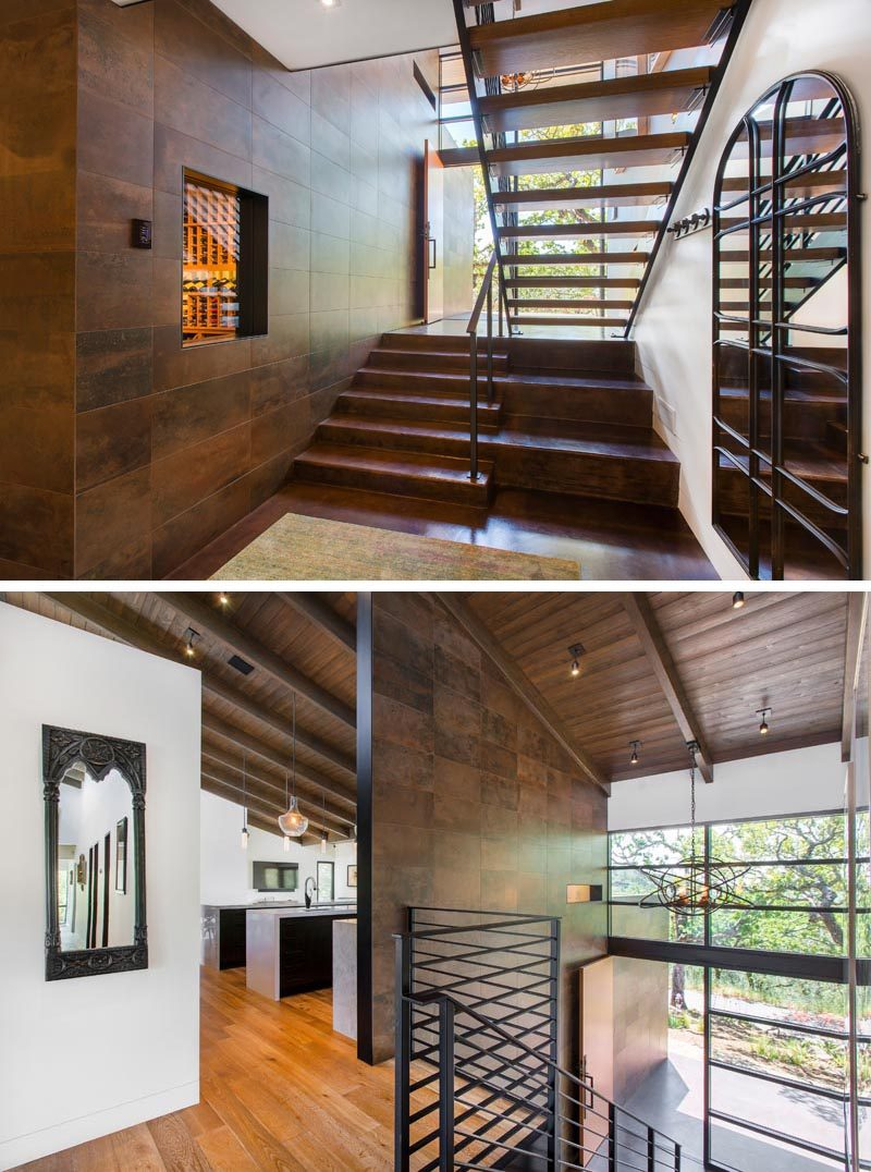 This modern house has stairs with a black steel handrail that connects the levels of the house. #ModernStairs #StairDesign