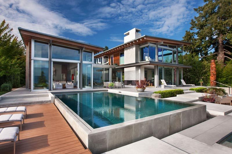 This northwest contemporary house has large windows, post and beam construction, a swimming pool with outdoor space, and a garden with a water feature. #ModernHouse #HouseDesign #Architecture #SwimmingPool