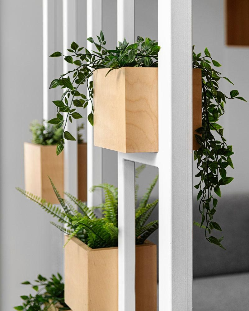 A white painted steel frame provides a place to display a few plants in wood boxes. #ModernPlanters #Decor