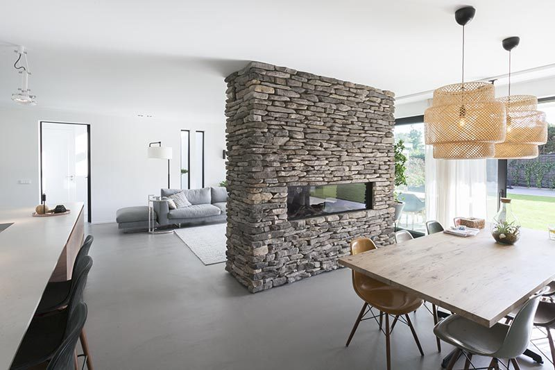 Apart from separating the dining area and living room, this stone accent partition is home to a linear fireplace on the dining room side, and on the opposite side, a built-in television with storage below. #StonePartition #StoneFireplaceSurround #StoneWall