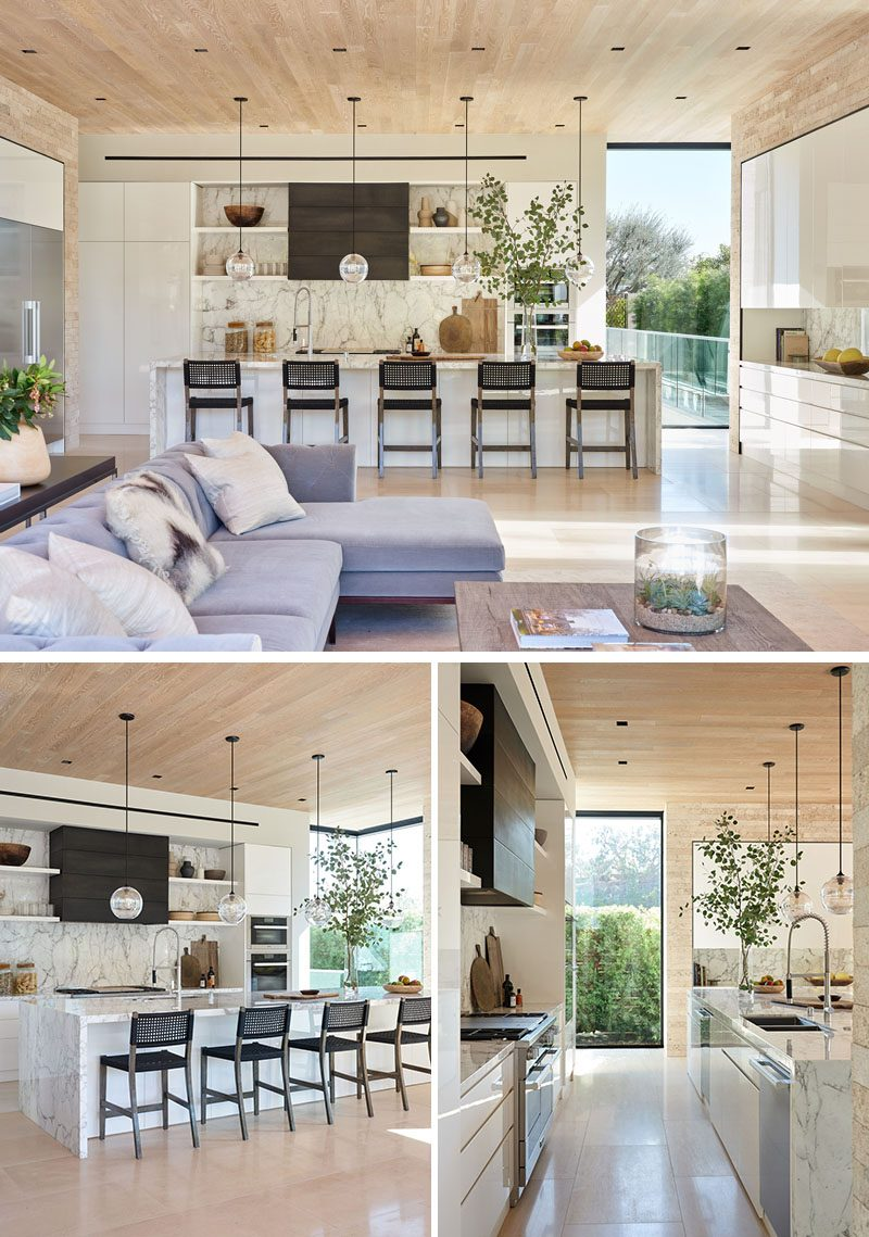 In the kitchen, a long kitchen island provides a place for five people to sit at, while four simple glass sphere pendant lights hang above it. #ModernKitchen #KitchenIsland #KitchenDesign