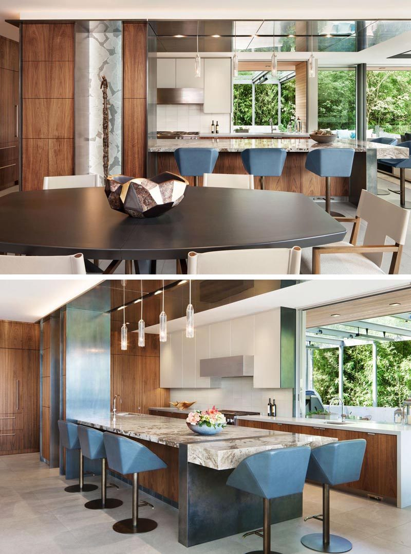 In this modern kitchen, a large peninsula with steel accents provide a place for casual seating. #ModernKitchen #KitchenDesign