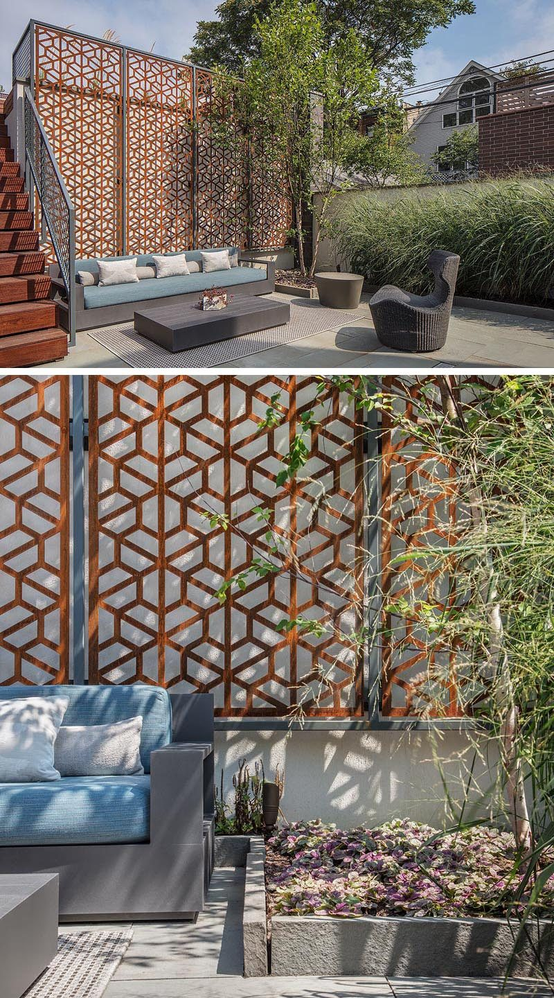 A modern but earthy vibe has been created with multi-level outdoor areas, field stone, and a custom raw steel screen, that has weathered over time and acts as a backdrop for a outdoor living room. #LandscapingIdeas #BackyardIdeas #YardIdeas #Terrace #OutdoorLounge