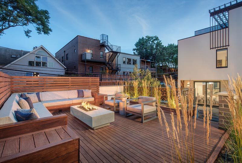 This rooftop deck has been furnished with a built-in corner sofa that has a small privacy screen, a pair of armchairs, a fire table, and tall plants. #RooftopDeck #Landscaping #Architecture #OutdoorSpace