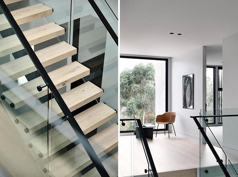 A glass and timber staircase leads to the bedrooms upstairs, while large black-framed windows complement the handrails. #ModernStairs #ModernStaircase #WoodTreads #BlackHandrail