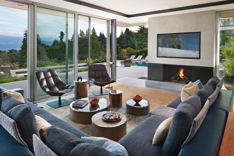 In this modern living space, floor to ceiling windows and doors open up to a patio that leads to the swimming pool. #LivingRoom #Fireplace