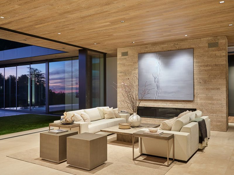 The social areas of this house include multiple living rooms. A neutral color palette has been used throughout the house, with the wood ceiling traveling from the interior to the exterior. #LivingRoom #Fireplace #GlassWalls #WoodCeiling