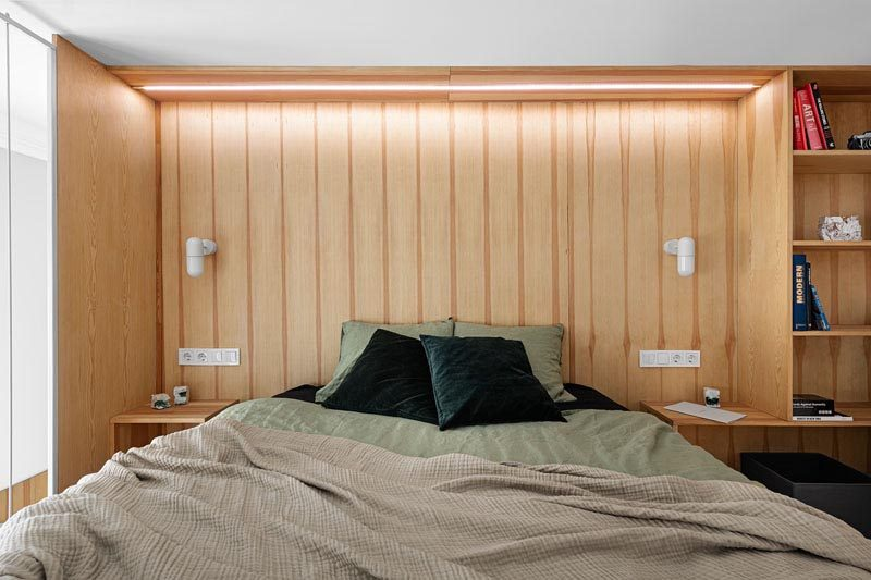 This apartment has a mezzanine that's home to a bedroom that has a wood-line wall that acts as a headboard, while simple lighting provides a soft glow. #ModernBedroom #InteriorDesign