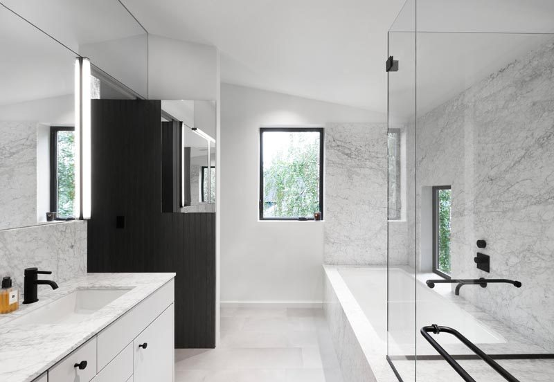 This modern master bathroom, which can be accessed from both the walk-through closet and the bedroom, has been clad in grey marble. A built-in bathtub and glass-enclosed shower line one wall of the bathroom, while the toilet is hidden from view behind a partition wall at the end. #MasterBathroom #EnsuiteBathroom #GreyBathroom #BathroomDesign #BuiltInBathtub