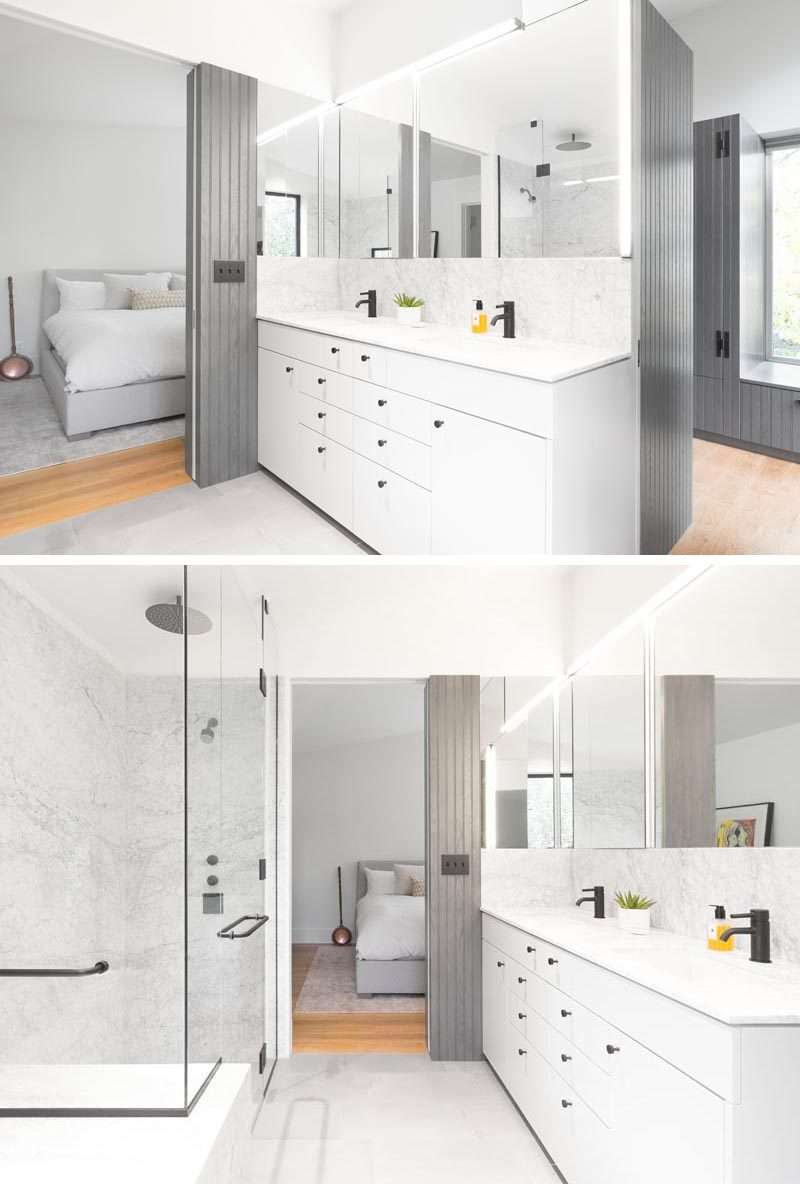 A minimalist white vanity with dual sinks and black hardware, sits below a mirror that wraps around the corner and is highlighted with accent lighting. #BathroomDesign #ModernBathroom #BathroomVanity