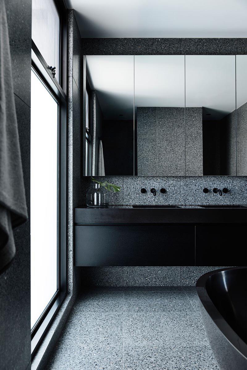 In this modern master bathroom, dark materials like black terrazzo were used to create a luxurious retreat with sense of calm. #MasterBathroom #BlackBathroom #BathroomDesign