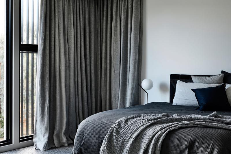 This modern bedroom has soft furnishings and long curtains to create a cozy atmosphere. #ModernBedroom #BedroomDesign