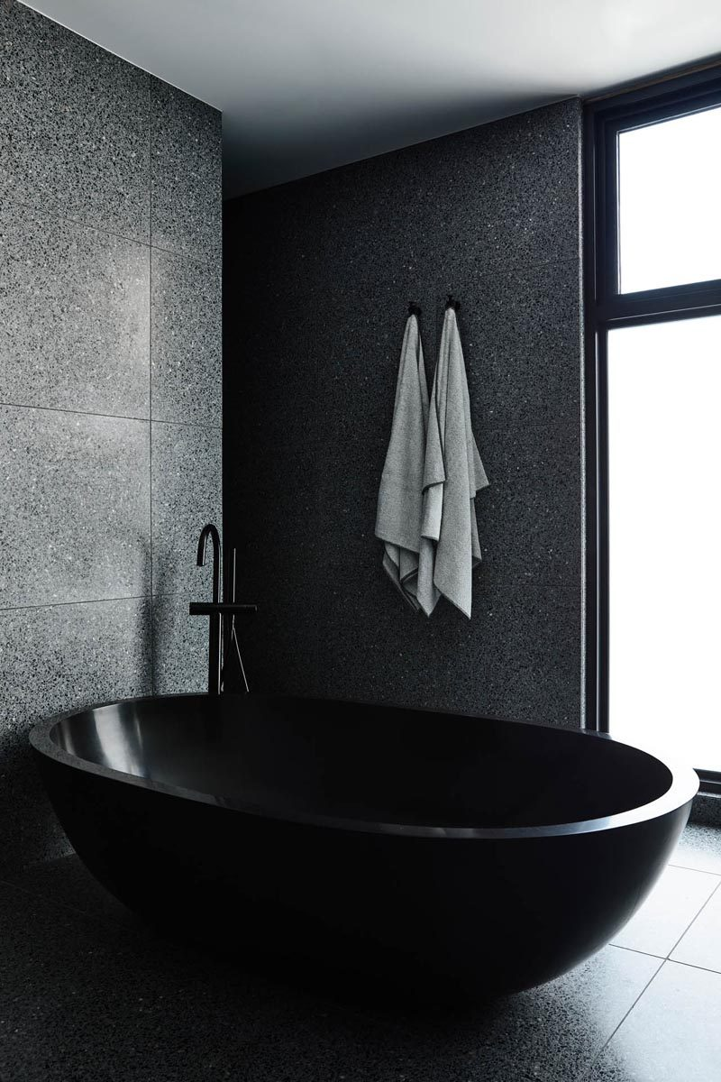 One stand-out feature in this modern master bathroom is the oval-shaped black freestanding bathtub. #BlackBathroom #BlackBathtub #InteriorDesign #ModernBathroom