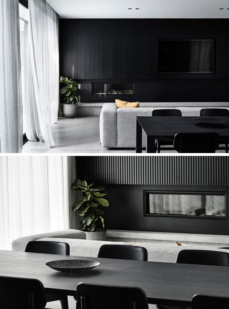 In this modern living room, a built-in linear fireplace and television blend in to the black accent wall, that adds a rich texture to the room with black timber battens. #BlackAccentWall #ModernLivingRoom #LinearFireplace #RecessedTV