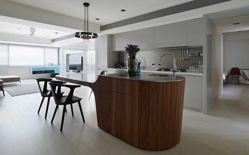 This modern multi-height kitchen island, which features a base that's been clad in vertical dark wood and a concrete countertop, has a small bar sink and food prep area at one end, and a cantilevered dining table at the other. #MultiHeightKitchenIsland #KitchenIslandDesign #CantileveredDiningTable #KitchenDesign #ModernKitchen #KitchenIslandIdeas