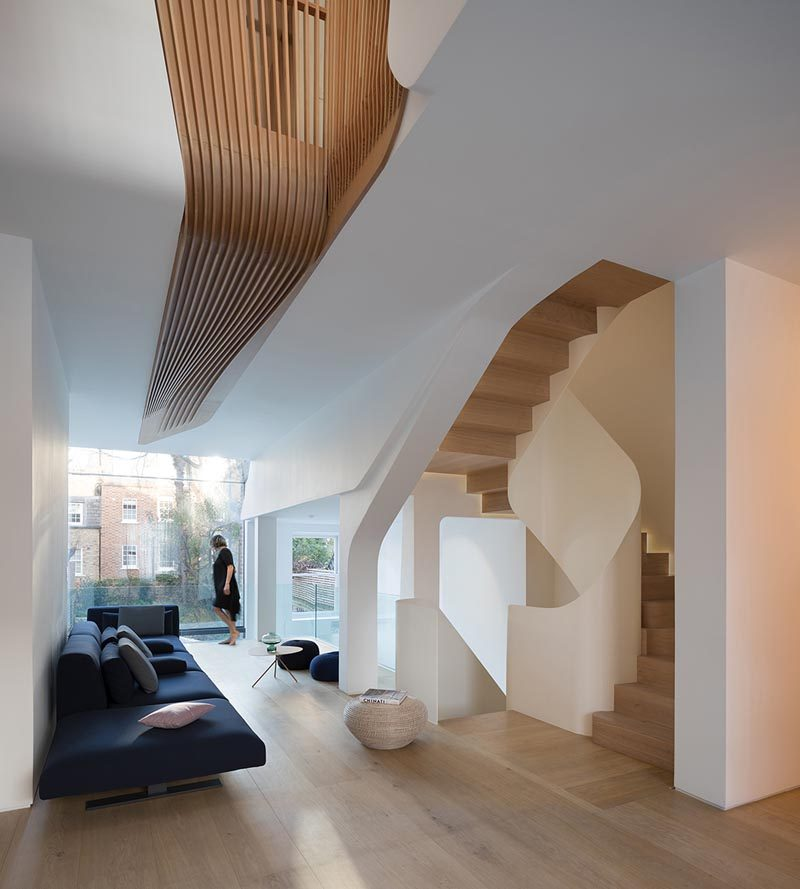 This modern house features wood floors, wood slat accents, and a spiraling staircase. #InteriorDesign #WoodFloors #Staircase