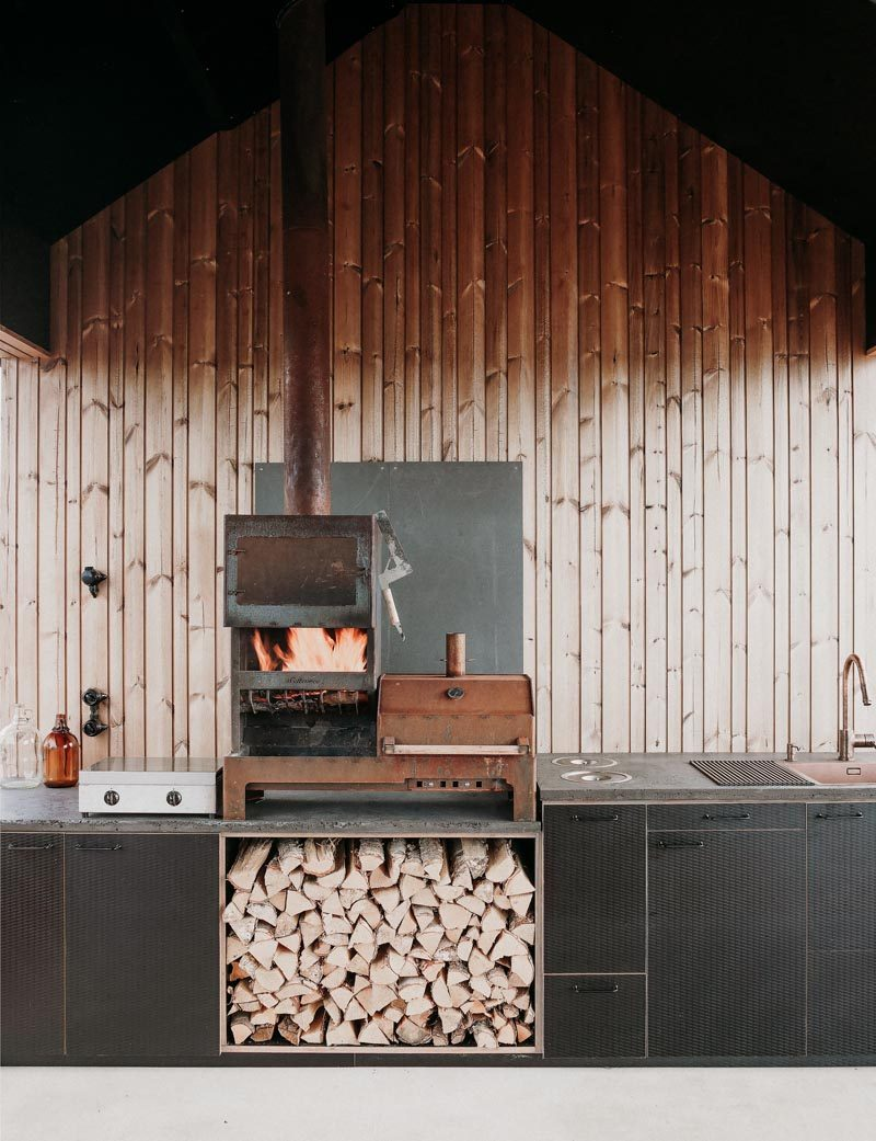 This outdoor kitchen has a row of black cabinets, a wood burning stove / bbq, and a sink. #OutdoorKitchen