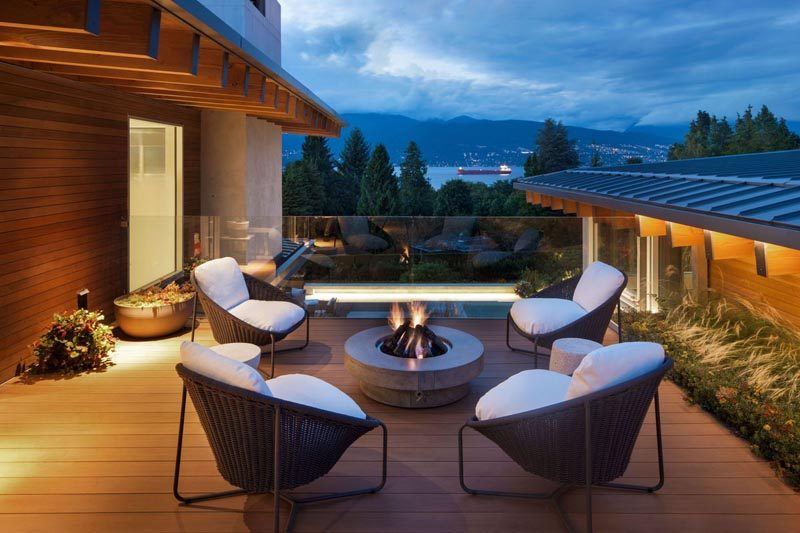 This modern house has an outdoor seating area with a fire bowl, and a glass safety rail allows for unobstructed views. #OutdoorEntertaining #FireBowl