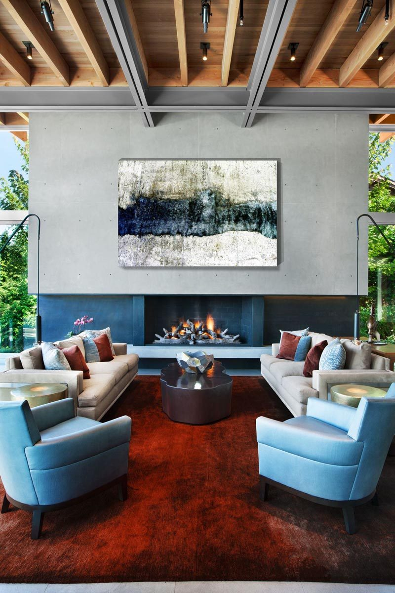In this modern living room, a large abstract art piece hangs above the fireplace, while the exposed ceiling adds a natural element to the space. #LivingRoom #Fireplace