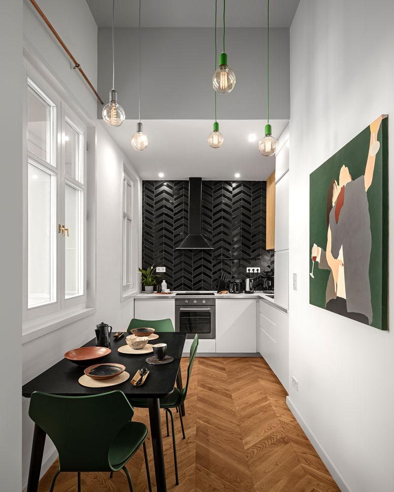 Gloss and matte black tiles have been used to create an accent wall in this modern kitchen, that features minimalist white cabinets and is complemented by the black dining table. #Kitchen #BlackTiles #WhiteCabinets