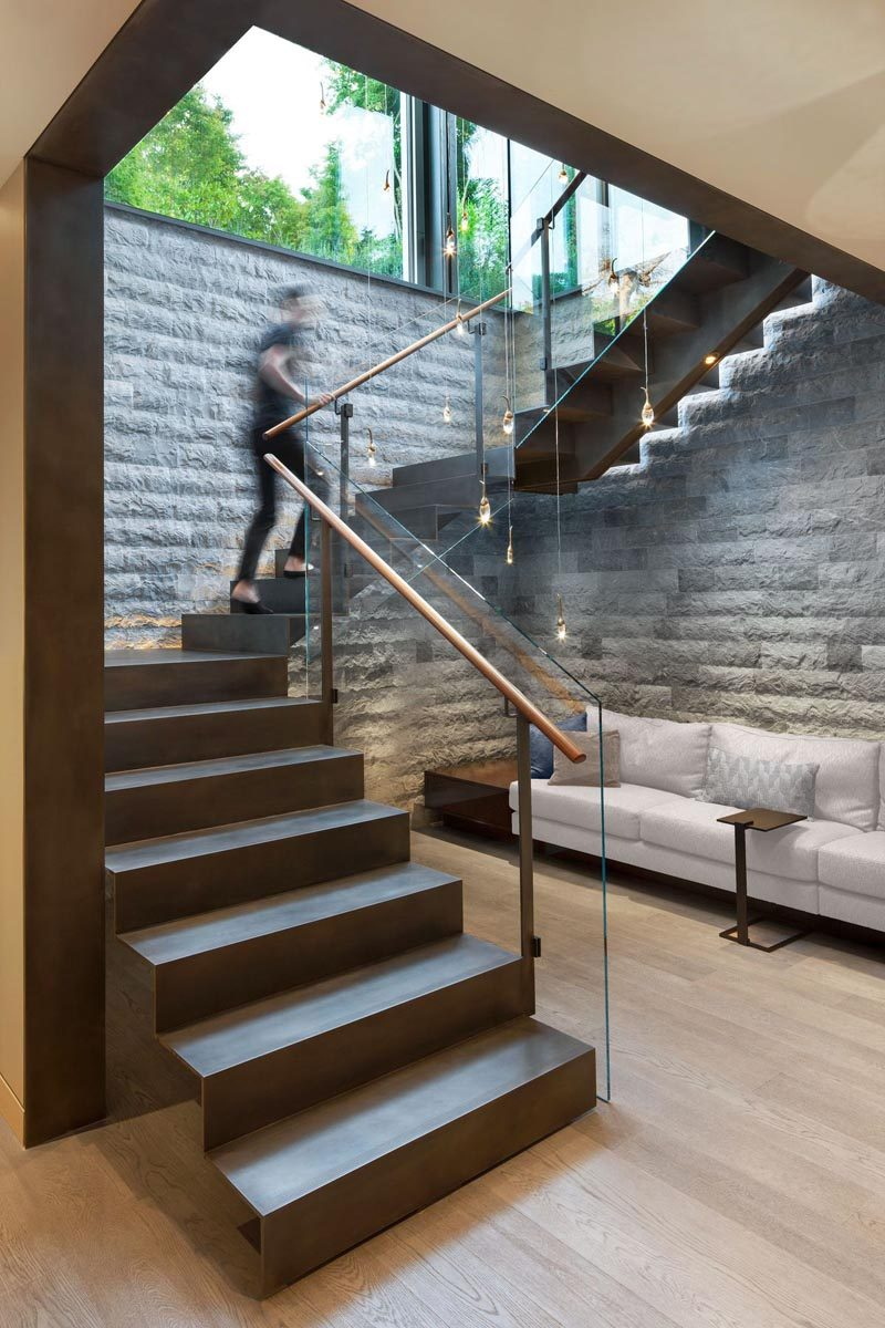 Steel stairs with glass railings lead down to the basement of this modern house. #SteelStairs #Stairs