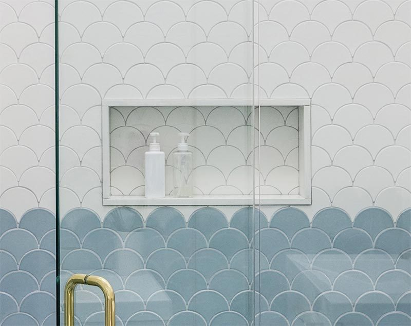 In this modern shower there's a built-in shower niche with a simple white frame that's tiled in the same tile that surrounds it. The shower niche provides a dedicated place to house shampoo bottles and soap, keeping the from gathering on the floor or in a shower caddy. #ShowerNiche #ModernShower #ShowerNicheIdeas